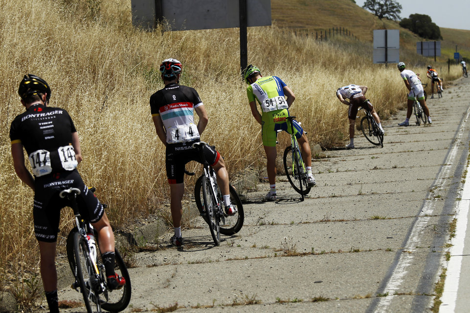 Riders in the peloton stop for a break during Stage 3 of the Tour of California in Tracy, California May 15, 2012.  REUTERS/Robert Galbraith  (UNITED STATES - Tags: SPORT CYCLING)